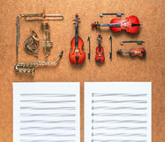 Set of five golden brass wind and four string musical orchestra instruments and sheet music lying near it. Music concept. Royalty Free Stock Photos