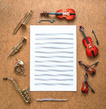 Set of five golden brass wind and four string musical orchestra instruments and sheet music lying between them. Royalty Free Stock Image