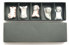 A set of five white clay cat shaped chopstick rest. A top down photo taken on a set of five white clay cat shaped chopstick rest against a white backdrop stock photo