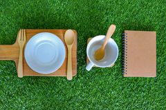 Set flatware style rustic have spoon, fork, empty plate and cup on green grass background. Set flatware style rustic have spoon, fork, empty plate and cup on is stock photos