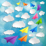 Set of flying colorful paper airplanes with clouds on the blue b Stock Photos