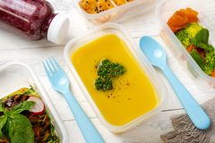 Set of food in plastic boxes with spoon and fork. Lentil soup in a plastic box on a plastic colored plate. on a white wooden table royalty free stock photo