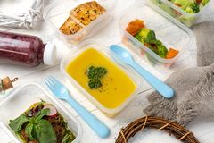 Set of food in plastic boxes on the table. Lentil soup in a plastic box on a plastic colored plate. on a white wooden table royalty free stock photo