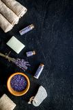 Set for foot spa with lavender. Flowers, spa salt, pumice stone, soap on black background top view copyspace Stock Photos