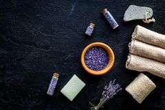 Set for foot spa with lavender. Flowers, spa salt, pumice stone, soap on black background top view copyspace Royalty Free Stock Photos