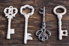 Set of four antique keys, one being different and upside down Stock Photos