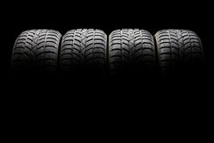 Set of four black car tires lined up horizontally. Studio shot of a set of four black car tires lined up horizontally in a dark ambient on black background Stock Image