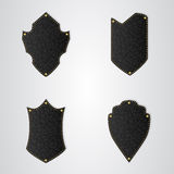 Set of four black leather shield with gold thread. Stock Photos