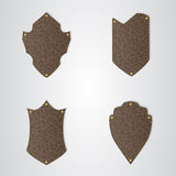 Set of four brown leather shield with gold thread. Stock Photos