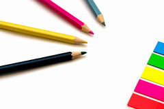 Set of four colorful crayons against stick notes. On white background, creativity concept royalty free stock photography