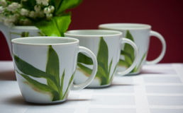 Set of four cups with lily of the valley on maroon Royalty Free Stock Image