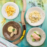 Set of four dishes Business lunch combo with kid`s railroad on blue wooden table. Top view royalty free stock image