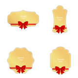 Set of four gold tag with red ribbons and bows. Royalty Free Stock Photography