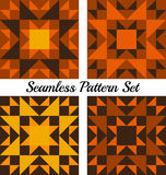 Set of four Halloween geometric seamless patterns with triangles and squares of orange, yellow, brown and black shades. Set of four abstract Halloween geometric Royalty Free Stock Images