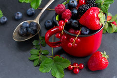 Set of  fresh berries. Fresh  berries with green  leaves   on black stone background Stock Photography