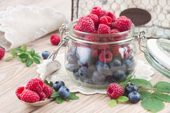 Set of  fresh berries. Set of fresh  raspberries and blueberries with green  leaves   on wooden table Stock Photos
