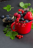 Set of fresh berries. Red cup with fresh berries on black stone background, low key stock photos