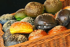 A set of fresh burger buns of different color with sesame seeds in the basket prepared for cooking at the street farm market Royalty Free Stock Image