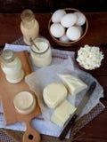 Set of fresh dairy products on wooden background: milk cheese cottage yogurt egg mozzarella ryazhenka feta. Set of fresh dairy products on wooden background Stock Image