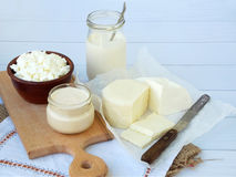 Set of fresh dairy products on wooden background: milk, cheese, cottage yogurt egg mozzarella, ryazhenka, feta. Royalty Free Stock Photo