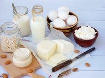 Set of fresh dairy products on wooden background: milk, cheese cottage, yogurt egg, mozzarella ryazhenka, feta. Set of fresh dairy products on wooden background Royalty Free Stock Images