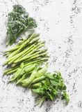 Set of fresh organic green vegetables - broccoli, green peas, asparagus, oregano on a light background. Food background, top view. Free space for text. Flat Stock Images