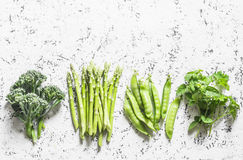 Set of fresh organic green vegetables - broccoli, green peas, asparagus, oregano on a light background. Food background, top view. Free space for text. Flat Stock Image