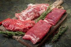 Set of fresh raw alternative beef steaks on a wooden Board: Denver, Skirt, Flank, Machete