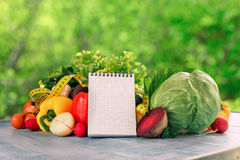 Set of fresh vegetables with measuring tape and blank notepad Stock Image