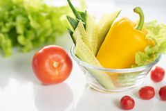 A set of fresh vegetables on a white plate, for the preparation of vegetable vegetarian salad. The background is white royalty free stock photography