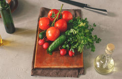 Set of fresh vegetables. On white table on a wooden kitchen board, top view. Branch tomatoes, bunch of parsley, radishes and cucumbers. Helpful and diet food Royalty Free Stock Images
