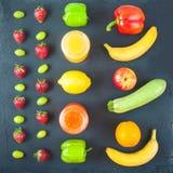 Set of freshly squeezed fruit juice, smoothies yellow orange green blue banana lemon apple orange kiwi grape strawberry on dark ba. Ckground Flat lay stock image