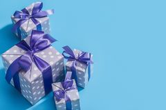 Stylish handmade gift boxes in purple packaging in polka dot, decorated with ribbons and bows, on a blue background. Copy space. Set of gifts for Christmas royalty free stock image