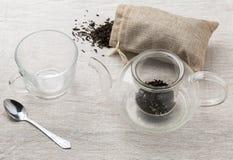 Set glass brewing teapot, teacup and bag of black tea Royalty Free Stock Photos