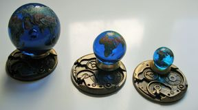 A set of 3 Glass earth geographically accurate in colourful detail. A set of 3 Glass earth marbles geographically accurate in colourful detail on a brass base Stock Photos