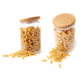 Set of glass jar filled with dry rotini pasta over isolated white background Stock Photo