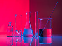 A set of glass labware on table. Red background with experimental glass containers and their reflection on a table in a blue light Royalty Free Stock Images