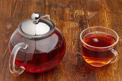Set of glass teapot and cup of black tea. Set of glass hot teapot and cup of tea on wooden table Stock Photography
