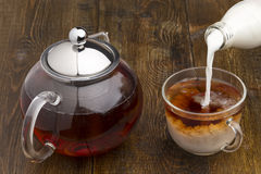 Set of glass teapot, teacup and bottle of milk. Set of glass teapot, cup and bottle of milk on wooden table stock images