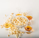 Set of glasses of single malt whisky, salty popcorn in a bowl an. D rozypane around, party set royalty free stock image