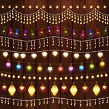 Set of Glowing Christmas Lights for Xmas Holiday. Greeting Cards Design. Wooden Hand Drawn Background. Light Bulbs Collection Stock Photos