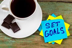 Set goals - inspirational handwriting in a green sticky note wit. H a cup of coffee and chocolate stock image