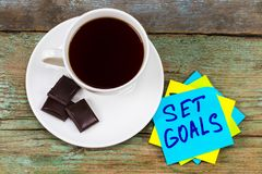 Set goals - inspirational handwriting in a green sticky note wit. H a cup of coffee and chocolate stock photo