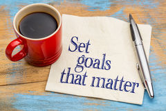 Set goals that matter on napkin. Set goals that matter advice or reminder - handwriting on a napkin with cup of coffee against gray slate stone background stock image