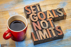 Set goals, not limits. Motivational advice in vintage letterpress wood type with a cup of coffee Royalty Free Stock Image