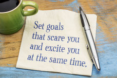 Set  goals that scare and excite you at the same time. Handwriting on a napkin with a cup of espresso coffee Royalty Free Stock Photos