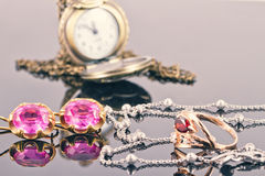 Set of gold jewelry with rubies and old copper pocket watch Stock Photo