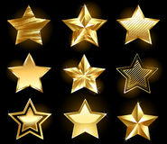 Set of gold stars. Set of gold, fine stars on a black background