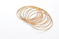 Set of golden adornment on white background. Collection of beautiful female bracelets isolated on white Royalty Free Stock Images