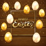 Set of golden Easter eggs on brown wooden background. Golden Easter eggs with decorative patterns and confetti. Gold Frame with lettering Happy Easter on brown Stock Photo
